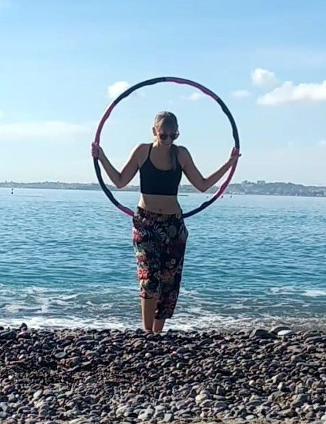 Woman holding a Hula Hoop standing by the sea