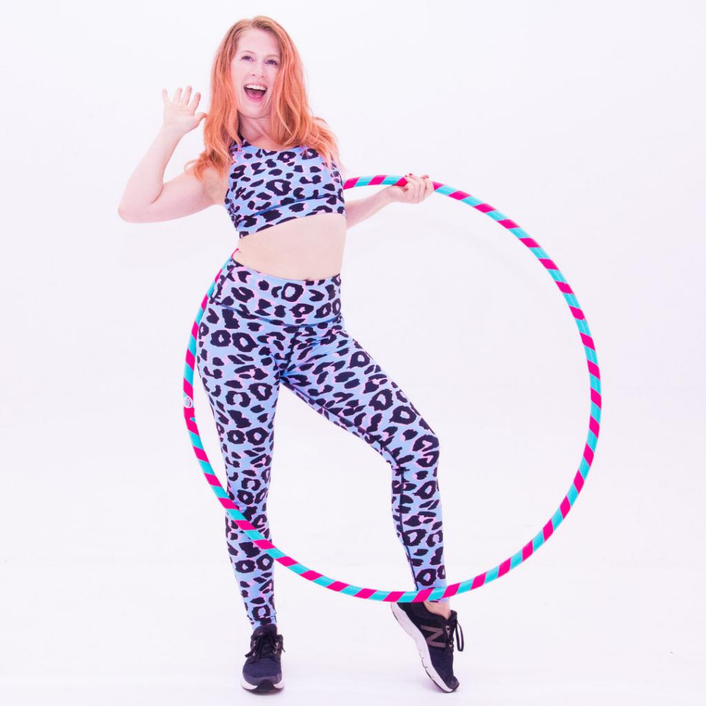 carla, hulafit instructor holds hulafit hulahoop in cool leopard leggings