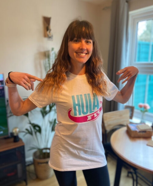Images show a woman with long brown hair modelling a HulaFit Instructor T-Shirt