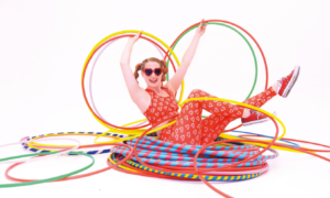 Carla, a white lady with red hair, is lying on a huge stack of hula hoops, in different sizes. She is wearing red sunglasses and holding up different sized hoops