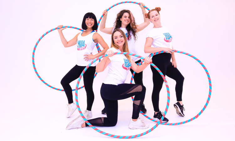 Four fmales in white tops and black leggings pose with their hoops in their hands