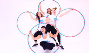 For smiley female hoopers pose with hula fit hoops. They are all wearing white hula fit tops and black leggings